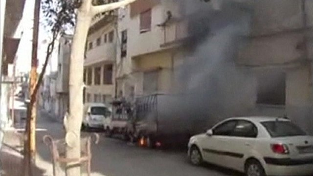 Vehicles on fire in front of apartment building in Syria