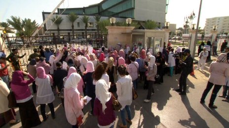 Women, many with their mouths' taped, attend a protest outside the interim prime minister's office in Tripoli