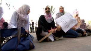 Women with their mouths' taped attend a protest outside the interim prime minister's office in Tripoli
