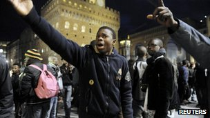 People reacts after two Senegalese vendors were killed in central Florence