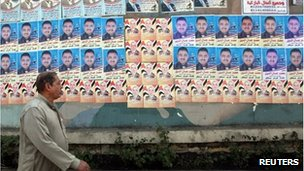 A man walks past election posters in Giza, Egypt (12 Dec 2011)
