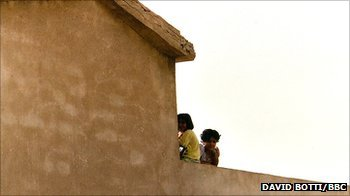 Young Iraqi girls sit on a roof