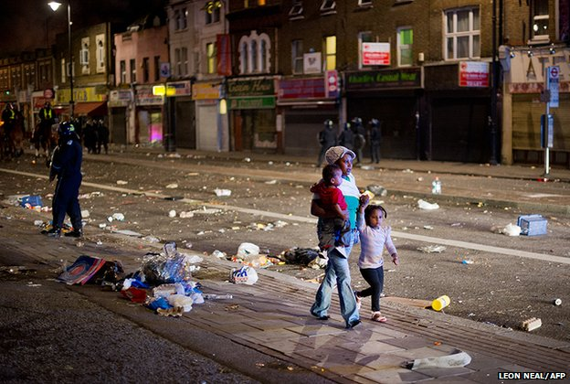 A woman walks through the debris with two children as riot police try to contain a large group of people on a main road in Tottenham, north London 6 August 2011