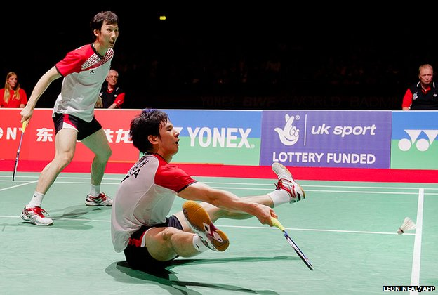 Ko Sung Hyun (seated) of Korea returns a shot to Mohammad Ahsan and Bona Septano of Indonesia (not pictured) during the men's doubles semi-finals from a rather unconventional position at the World Badminton Championships at Wembley Arena