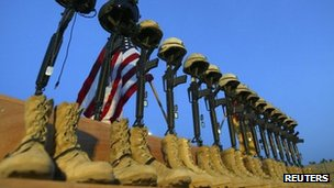 A row of US Army helmets perched on M-16 rifles at a memorial at Al-Asad air base in November 2003