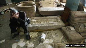 Iraq's National Museum Deputy Director Muhsin Hasan holds his head in his hands as he sits on destroyed artefacts in Baghdad (13 April 2003)