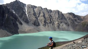 Tourist walks along banks of Lake Ala-Kul, in mountains of Kyrgyzstan