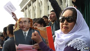 Supporter of Kyrgyz opposition waves demaged portraits of President Akayev in front of presidential palace in Bishkek in March 2005, after it was captured by opposition