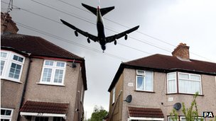Low-flying plane passing over houses  outside Heathrow Airport