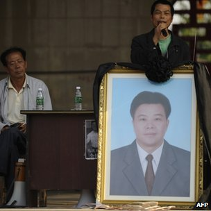Protesters show a portrait of deceased village leader Xue Jinbo