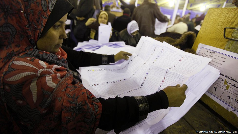 Egyptian workers count votes at a counting centre at Imbaba in Giza