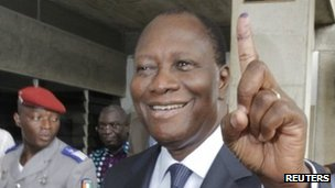 Ivory Coast&#039;s President Alassane Ouattara displays his inked stained finger after casting a ballot at a polling station in Cocody, December 11, 2011. 