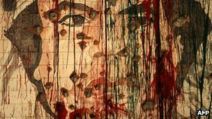 A defaced portrait of then-fugitive Libyan leader Col Muammar Gaddafi is pictured in Tripoli on 1 September 2011 