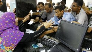 Libyans try to get cash from their accounts at a bank in Tripoli. File photo