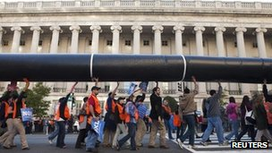 Protesters carry a mock pipeline in protest against the Keystone XL pipeline project 6 November 2011