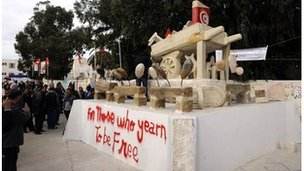 People gather by a statue representing the cart of Mohamed Bouazizi in Sidi Bouzid, 17 December 2011
