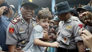An Indonesian police carries a young survivor while officials transfer them to an immigration office, in Watulimo on 18 December 2011