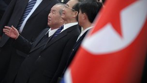 North Korean flag with leaders in the background