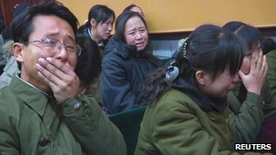 Employees of Pyongyang 326 Electric Wire Factory mourn over the death of North Korean leader Kim Jong-il, as they gather in a conference hall in Pyongyang in this still image taken from video.