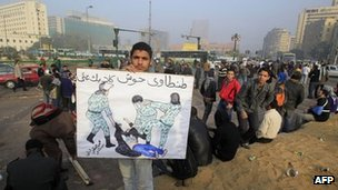 Man holds a sketch showing Egyptian soldiers dragging a woman on the ground by her clothing, exposing her underwear (19 December 2011)