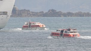 Tenders operating from a cruise ship moored off Guernsey with Sark in the background