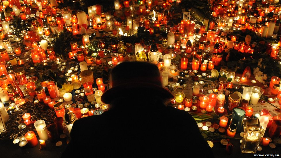 A woman is silhouetted in front of candles in Wenceslas Square, Czech republic