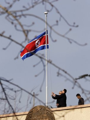 Staff lower the North Korean national flag to mourn the death of North Korean leader Kim Jong-il, on the roof of the its embassy in Beijing December 19, 2011.