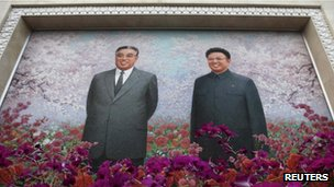 A file picture shows a painting featuring North Korean leader Kim Jong-il (R) and his father Kim Il Sung