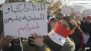 "A child holds a poster saying ""The children of Moadamieh and Daria are mourning their childhood"", during a protest against President Bashar al-Assad near Damascus (18 December 2011)"