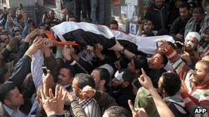 Mourners carry the body a protester killed in clashes in Cairo (19 December 2011)