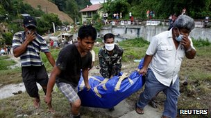 A soldier and local government workers carry a body bag containing the body of a flood victim for burial in Iligan city in southern Philippines