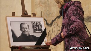 A mourner lays a Christmas angel at a photograph of former Czech President Vaclav Havel