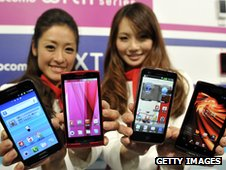 Two models hold four smartphones