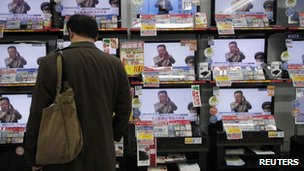 A man in Tokyo looks at TV screens with reports of Mr Kim&#039;s death