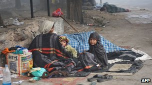 An Indian homeless family sleeps on a roadside on a chilly morning in New Delhi on December 19, 2011.