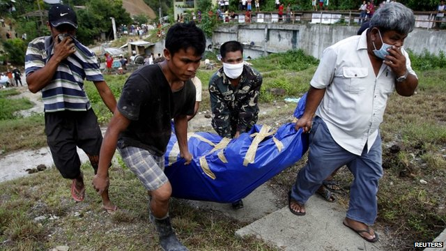 People carry body of flood victim