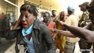 An injured supporter of ousted Ivorian President Laurent Gbagbo in Abidjan on 30 November 2011)