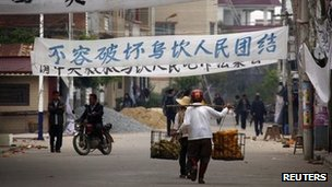 Residents walk down a street lined with protest banners in the Wukan Village in Lufeng, southern China, 20 December 2011