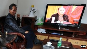 Villagers watch as Zheng Yanxiong, Communist Party Secretary of Shanwei, speaks on TV, in the village of Wukan, 20 December 2011