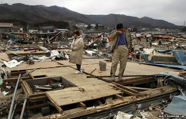 Keijo Nakamura (right) and his wife Haruka react as they stand on the remains of a relative's home in Ofunato
