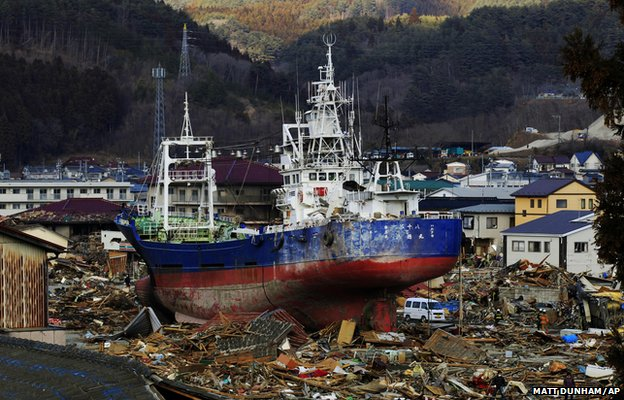 A large vessel stands amongst debris after being washed ashore in Kesennuma