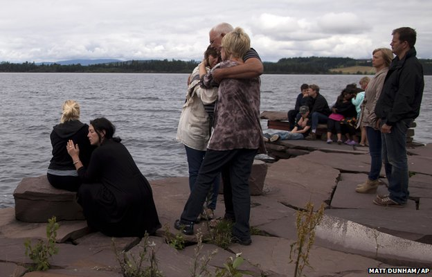 People gather to observe a minutes silence across the water from Utoya island where Anders Behring Breivik killed at least 68 people, many of whom were teenagers attending a summer youth camp on the island