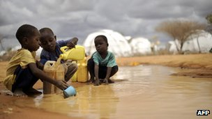 Somali boys fetching water from a puddle that formed after rain in Dadaab, Kenya.