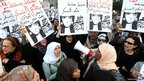 Egyptian women hold signs calling for the fall of the military council during a protest in downtown Cairo