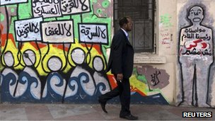 A man walks past graffiti near Tahrir Square in Cairo