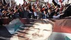 Syrians hold a large poster depicting Syria's President Bashar Assad during a rally in Damascus, Syria