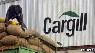A man gathers bags of cocoa beans at the Cargill factory in San Pedro, Ivory Coast 29 October 2004