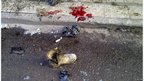 A soldier's boot and blood stains are seen on the ground after a bomb attack in Alawi district in central Baghdad