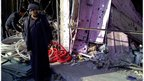 A man stands near shops damaged in a bomb attack in Alawi district in central Baghdad