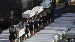Philippine Navy soldiers load coffins to be transported to Mindanao onto a navy ship which docked in Manila on 20 December 2011